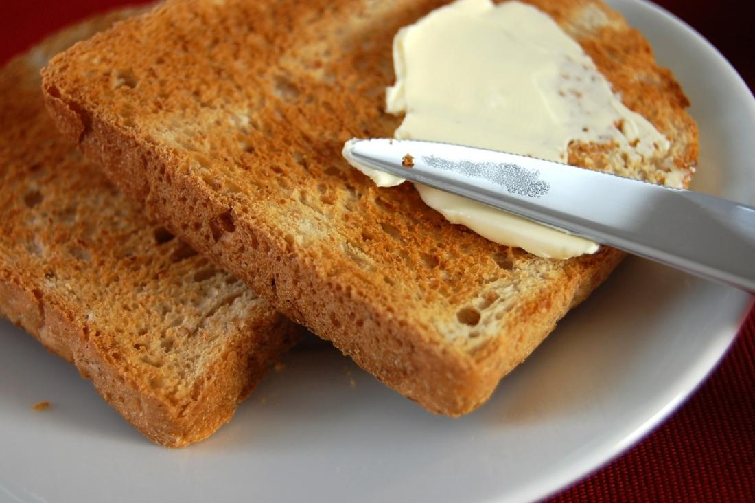 toast-on-a-plate-being-buttered-with-spread